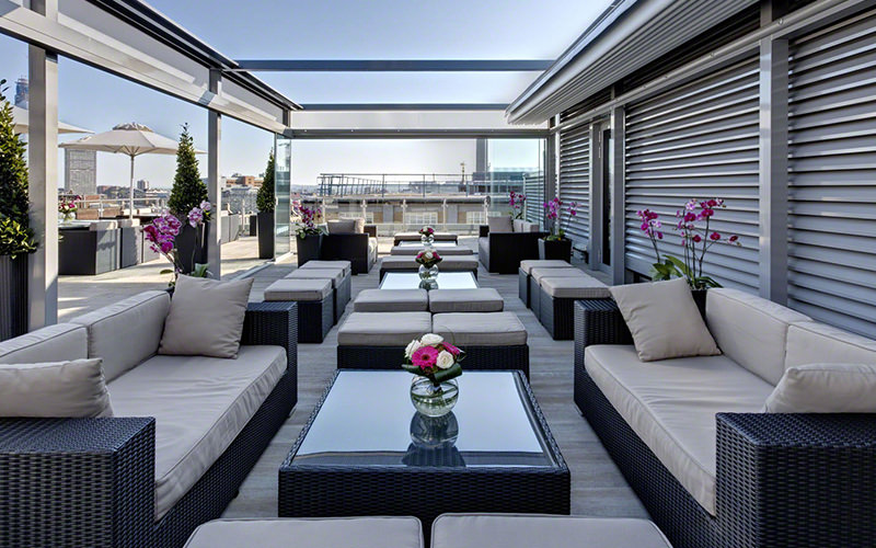 White sofas and tables on the rooftop terrace of The Grange Hotel St Pauls