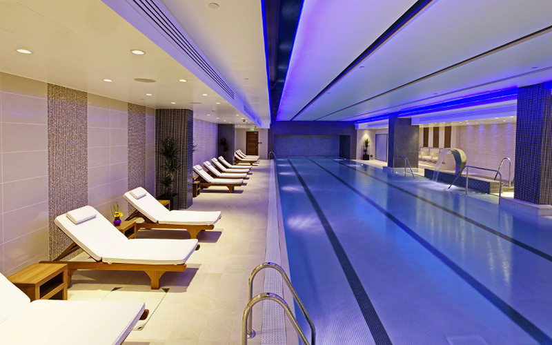 Indoor swimming pool at The Grange St Pauls, with white sun loungers lined up along the side