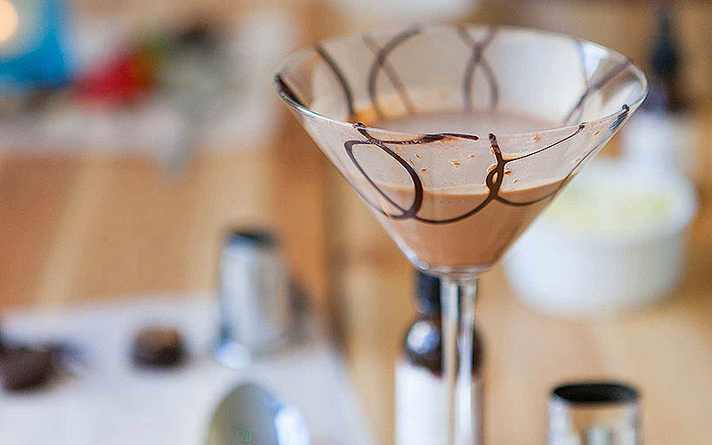 Chocolate Martini in a martini glass decorated with chocolate swirls.