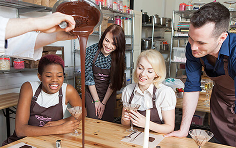 3 ladies and a man watch as chocolate is poured onto the table.