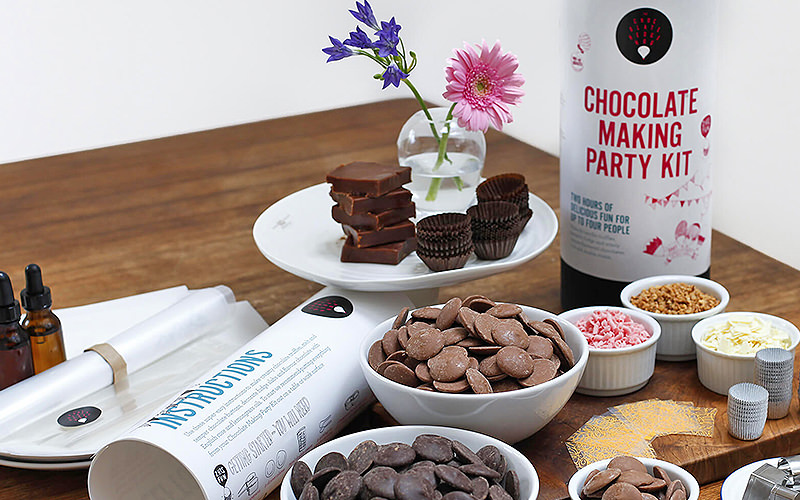 A table full of a chocolate making party kit, including multiple types of chocolate and decoration.