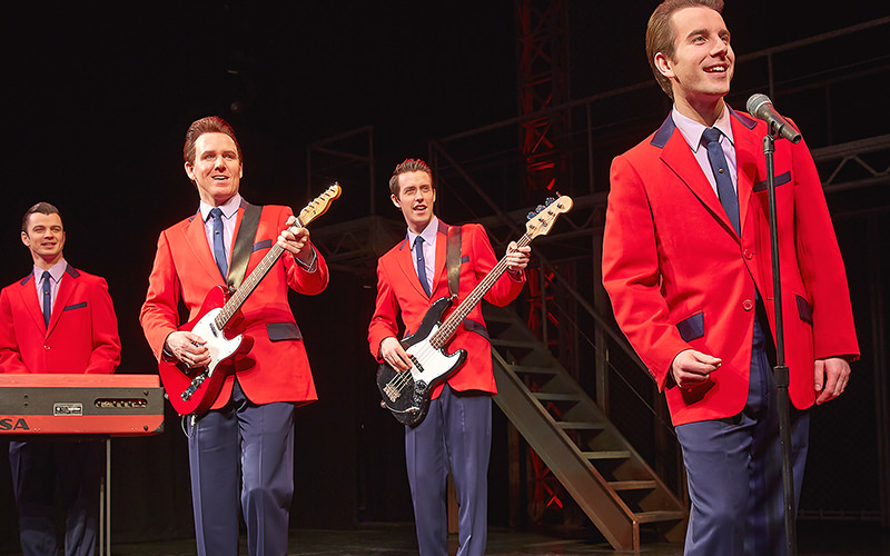 4 members of the Jersey boys - one singing, two playing guitar and one playing the keyboard.