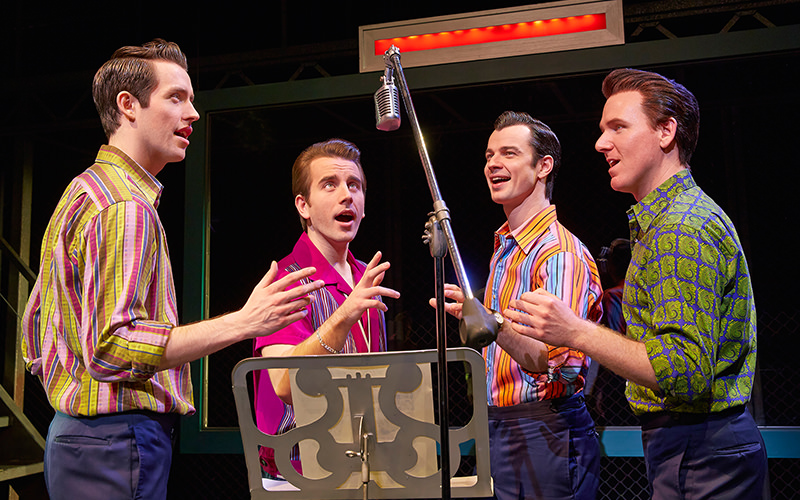 4 men in the Jersey Boys sing gathered around the microphone.