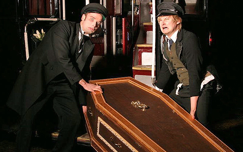Two men lifting a coffin.