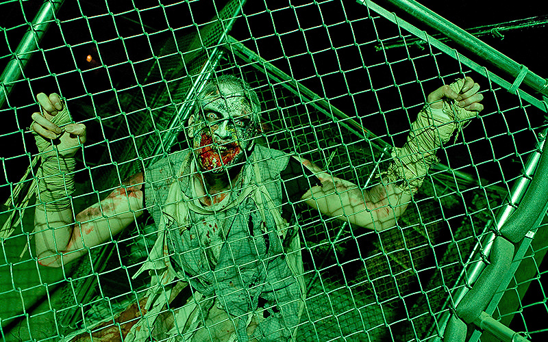 A man dressed as a zombie and clinging onto a chain link fence