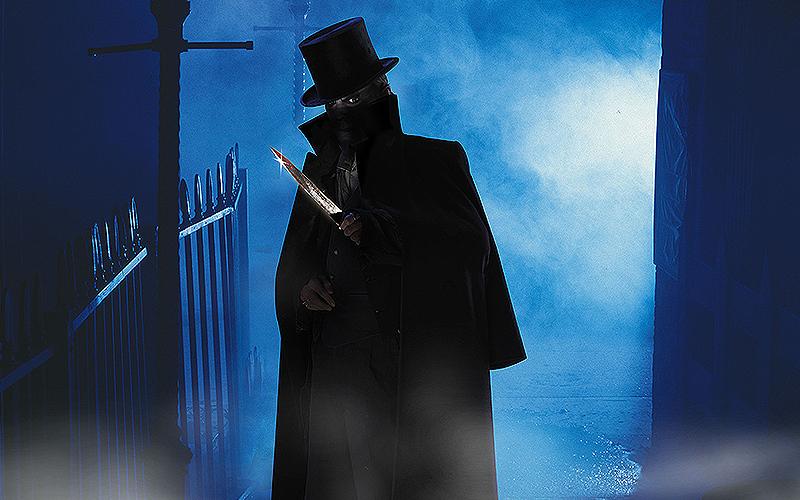 Man in long black cloak and hat, in dark alleyway holding a knife