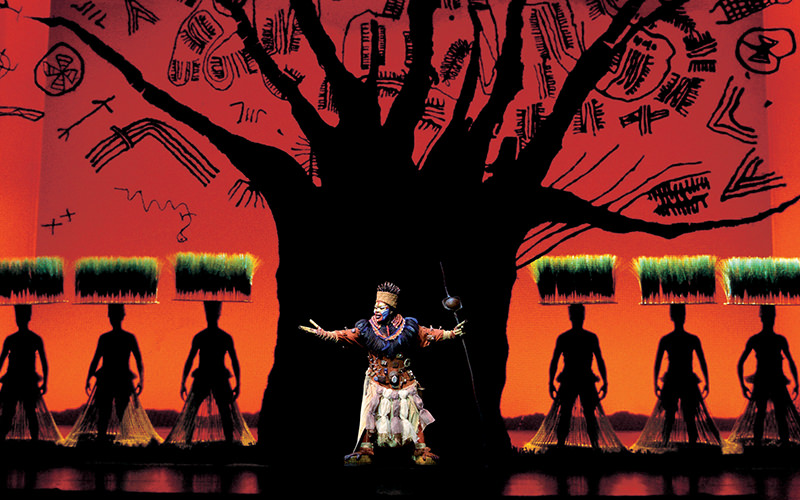 A male actor on stage performing at The Lion King the Musical