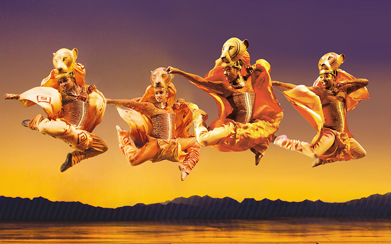 Four actors jumping on stage at The Lion King the Musical