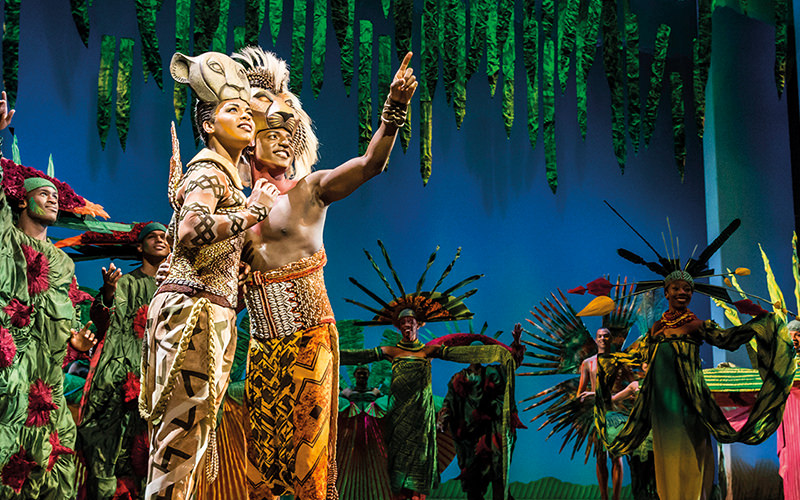 Two actors looking up and performing on stage from The Lion King the Musical