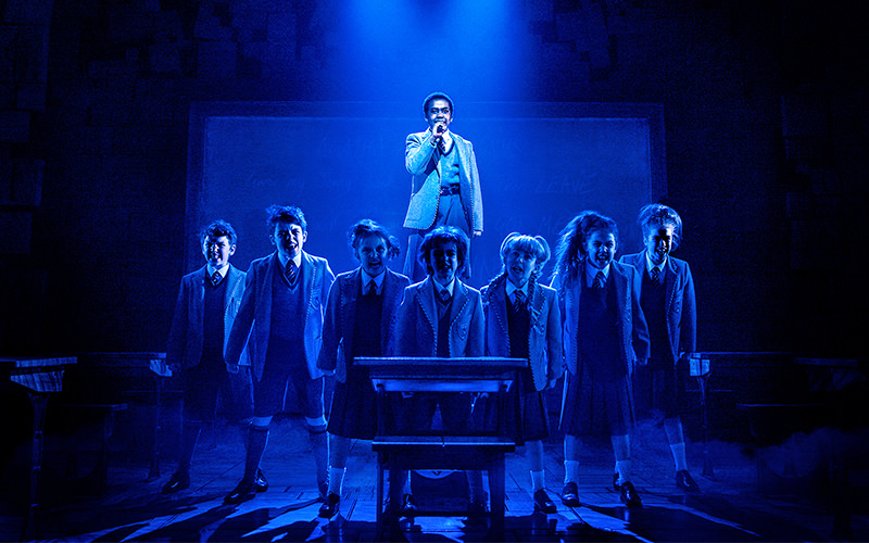 Children lined up, with a boy singing in the background, on stage at Matilda the Musical