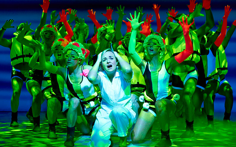 A woman holding her head, with actors in the background, on stage at Mamma Mia the Musical