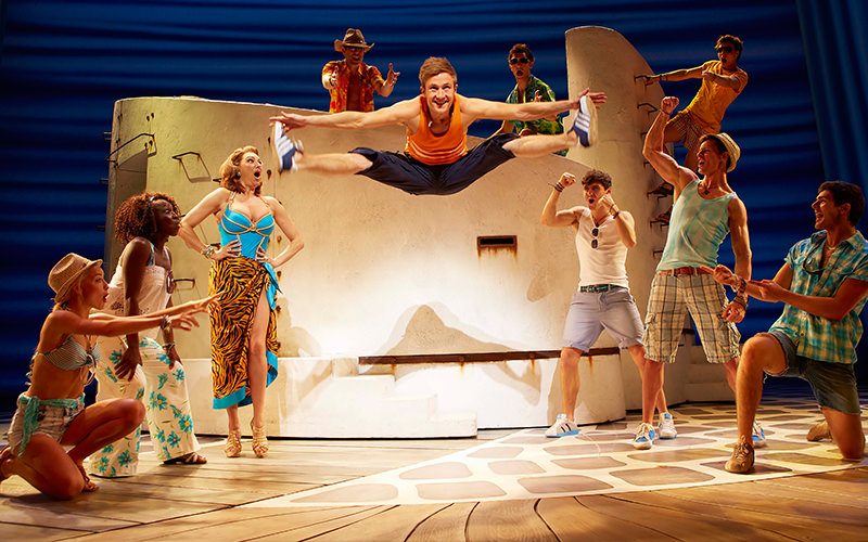 A man jumping in the air, with actors in the background, on stage at Mamma Mia the Musical
