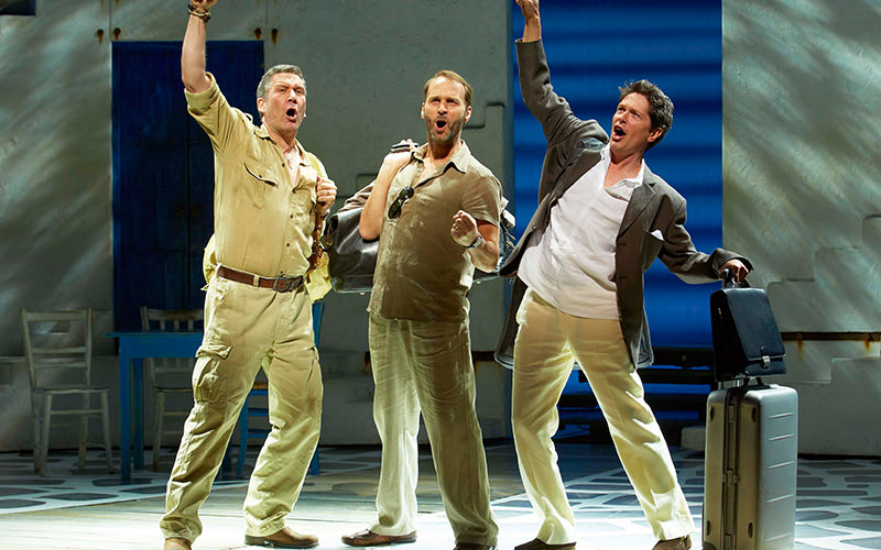 Three men singing on stage at Mama Mia the Musical