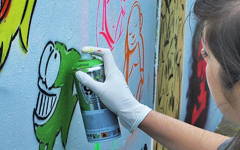 Close up of a girl spray painting on a wall
