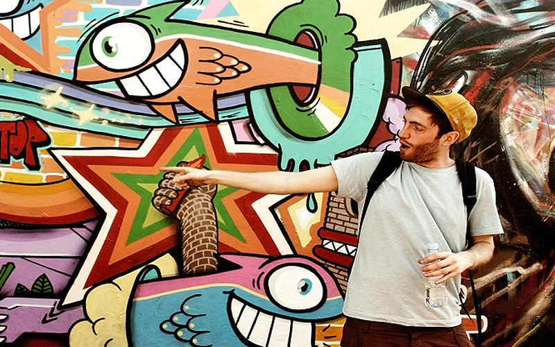 A man pointing at a fish graffiti filled wall in London