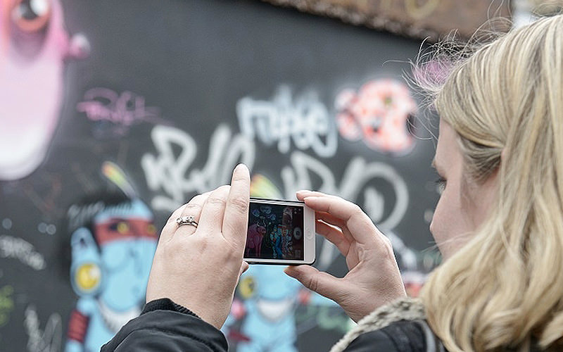 A woman taking a photo on her phone of grafitti on a wall in London