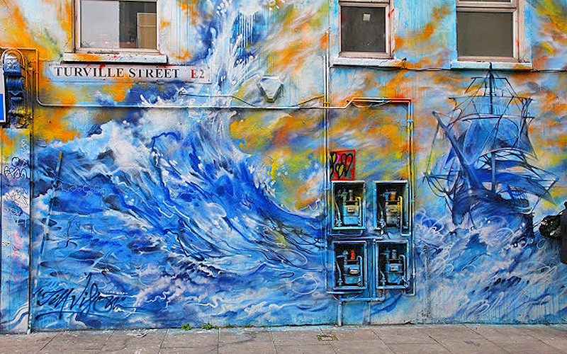 Seascape grafitti filled wall, with blues, whites and yellows underneath a Turville Street sign