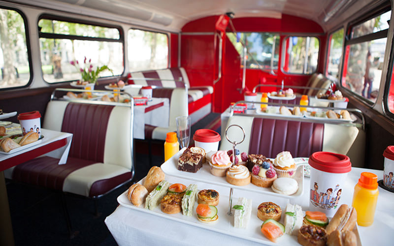 Afternoon tea set up on a bus on a white table, with other tables and chairs in the background