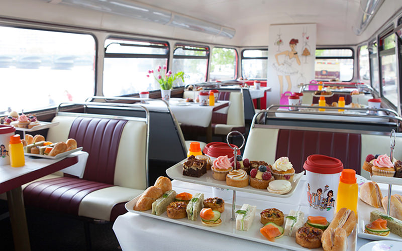 Afternoon tea laid out on two tables on a bus, with tables and chairs set out in the background