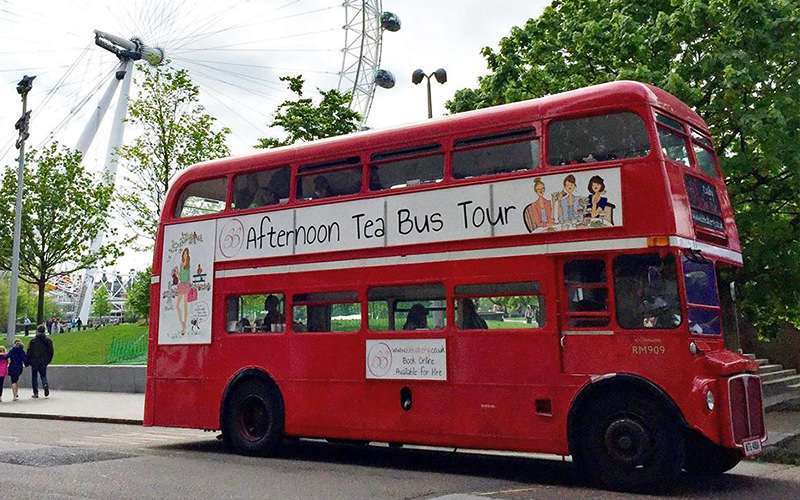 The red double decker, afternoon tea bus parked up, with the London Eye in the background