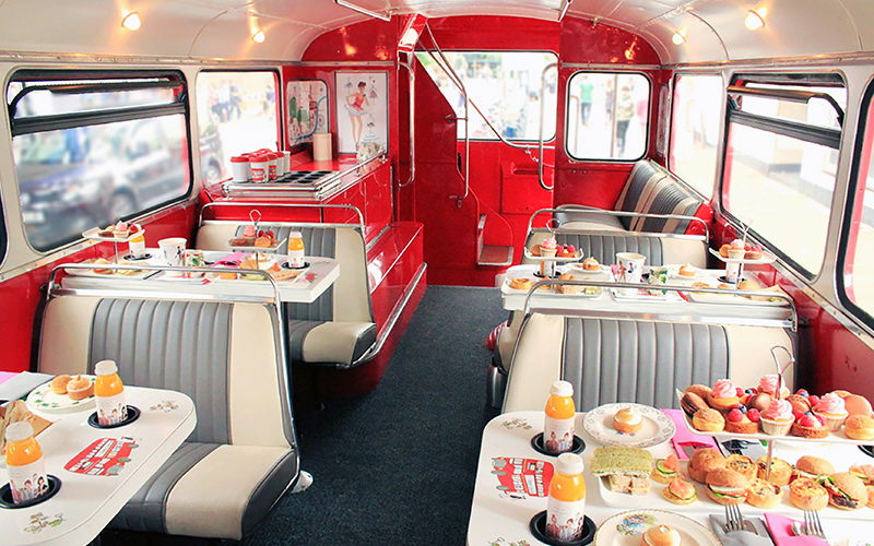 Tables and chairs lined up along the sides of a red bus, with afternoon tea laid out on the tables