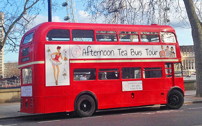 The red bus from the London Bus Afternoon Tea Tour on the road, with The London Eye in the background