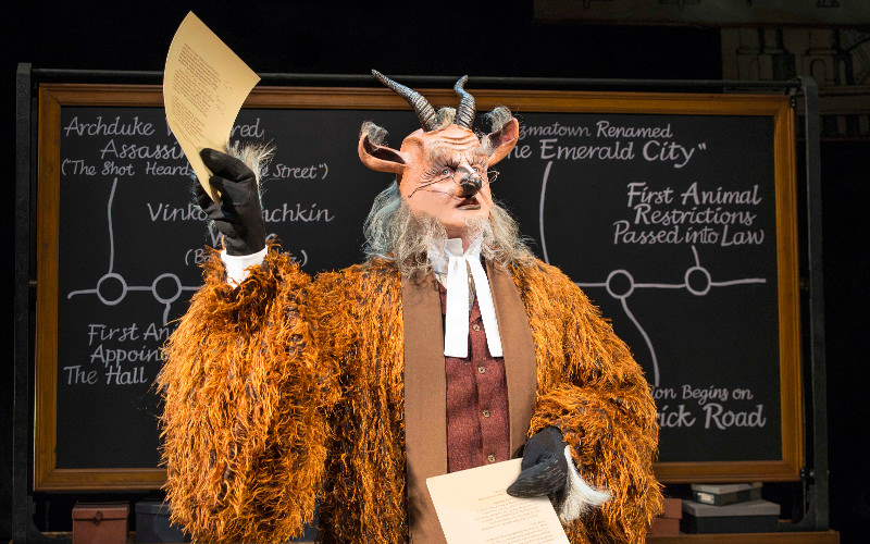 A man dressed as a goat and holding a sheet of paper in front of a blackboard during Wicked the Musical