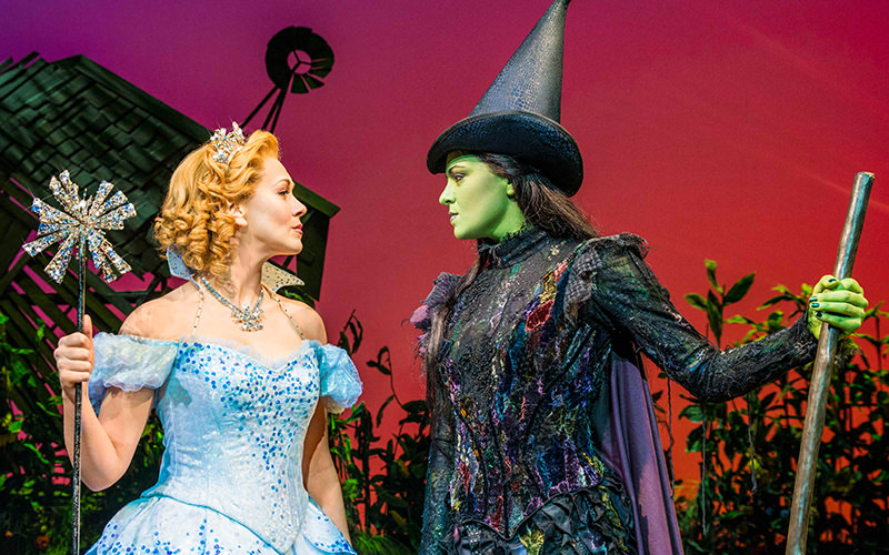 The fairy godmother and green wicked witch facing each other on stage for Wicked the Musical