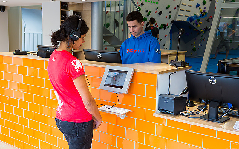 orange brick reception desk with computer login