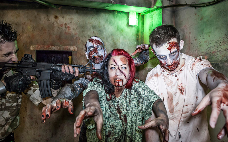 Three people dressed as zombies with a man holding a gun to a female zombie's head