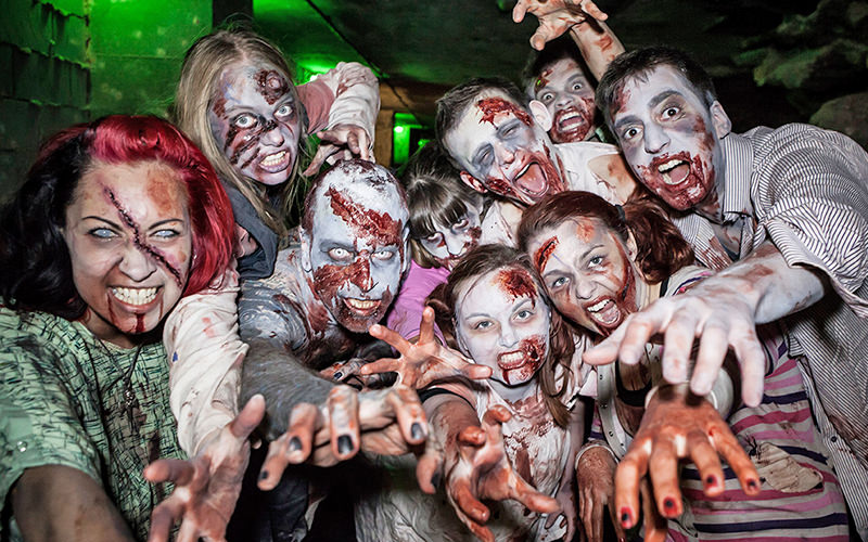A group of people dressed as zombies and reaching towards the camera