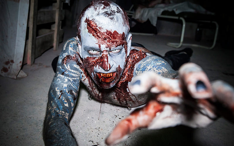 A man on the floor and reaching towards the camera whilst dressed as a zombie