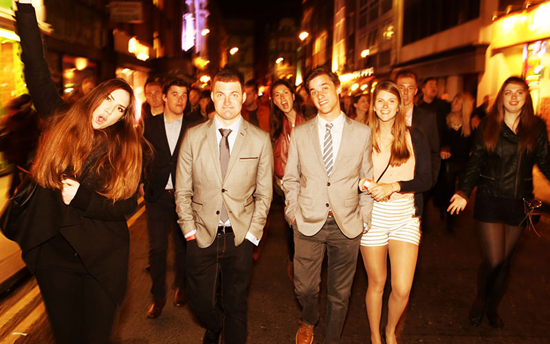 A group of young people dressed smartly, walking towards the camera in the street