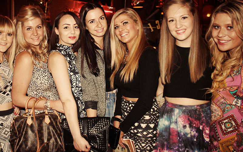 A group of young women posing for a photo on a night out