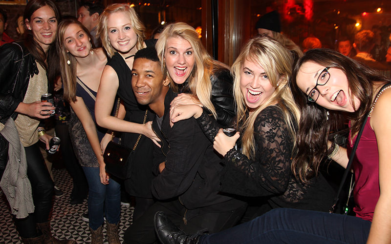 Six girls and one man in the middle, all smiling at the camera