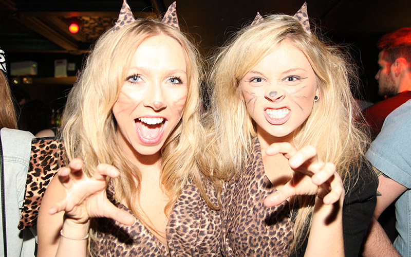 Two girls dressed as leopards, each striking an animal like pose