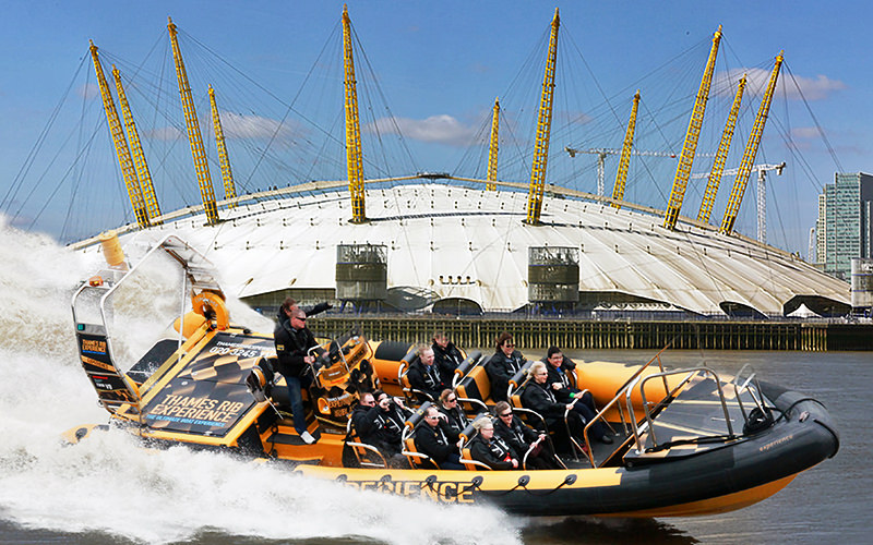 A speedboat full of people, with The O2 Arena in the background