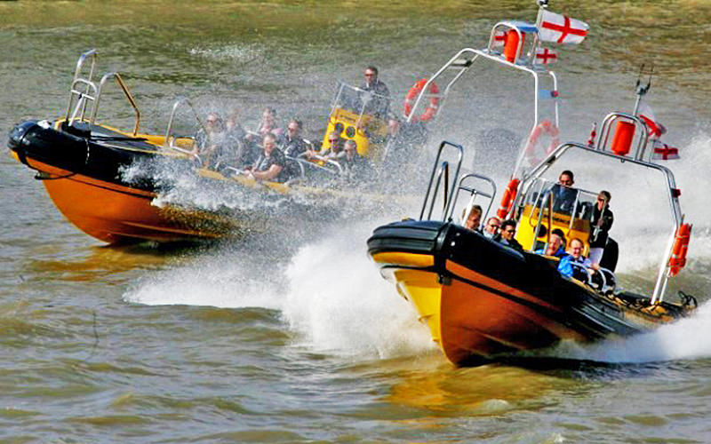 Two speedboats full of people riding the waves