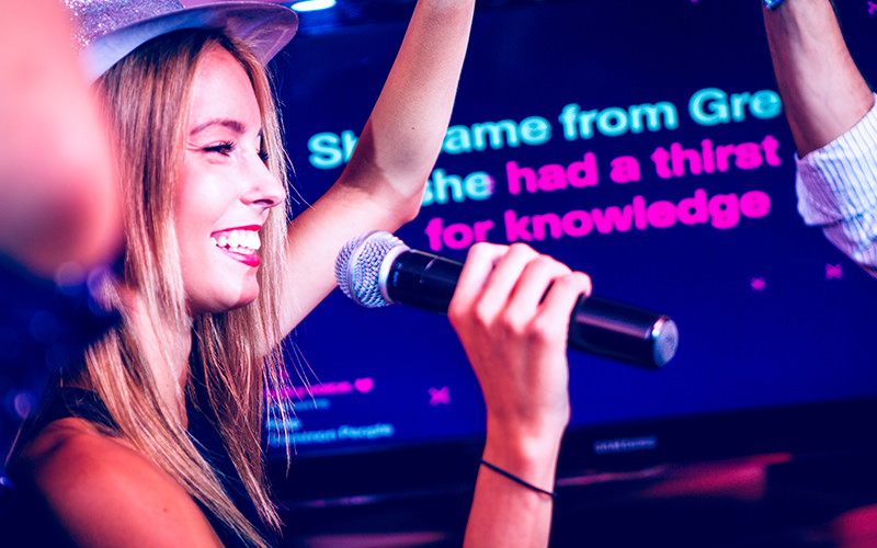 A woman wearing a hat and singing into a mic, with a TV displaying song lyrics in the background
