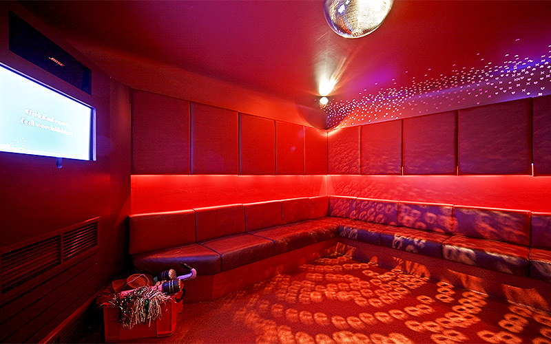 A lit up, empty red karaoke room with leather seats lining the walls, and a TV screen in the corner