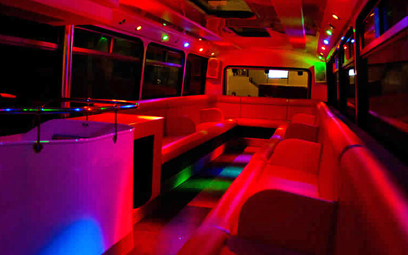 Interiors of the party bus, including seating illuminated in neon colours