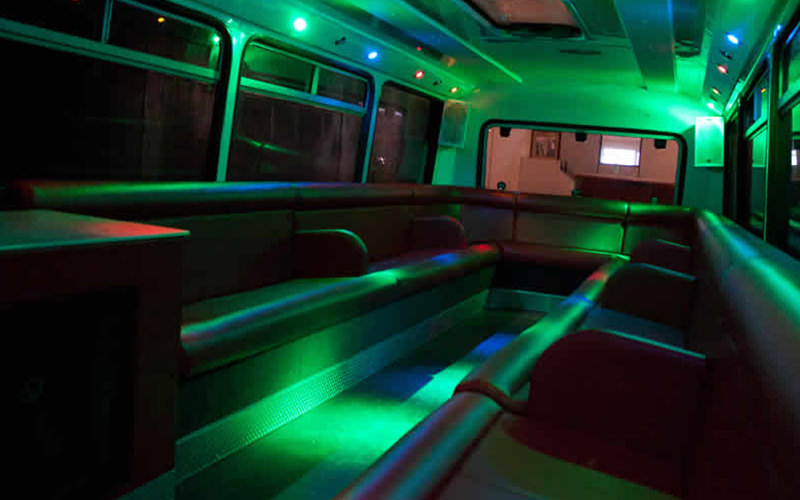 Interiors of the party bus, with dark seats and green lighting