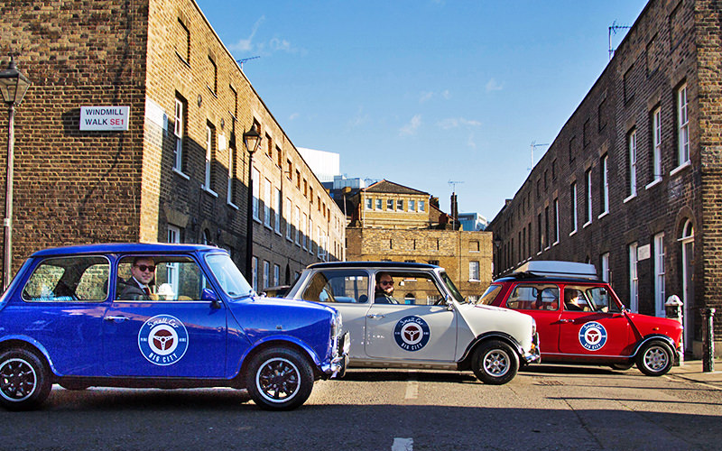 Three Mini Coopers in a street in London, under a bright blue sky