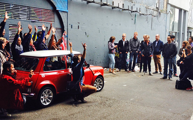 A red Mini Cooper with people surrounding it