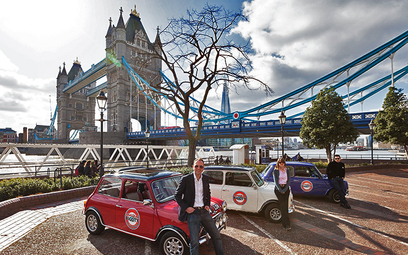 Red, white and blue Mini Coopers next to Tower Bridge