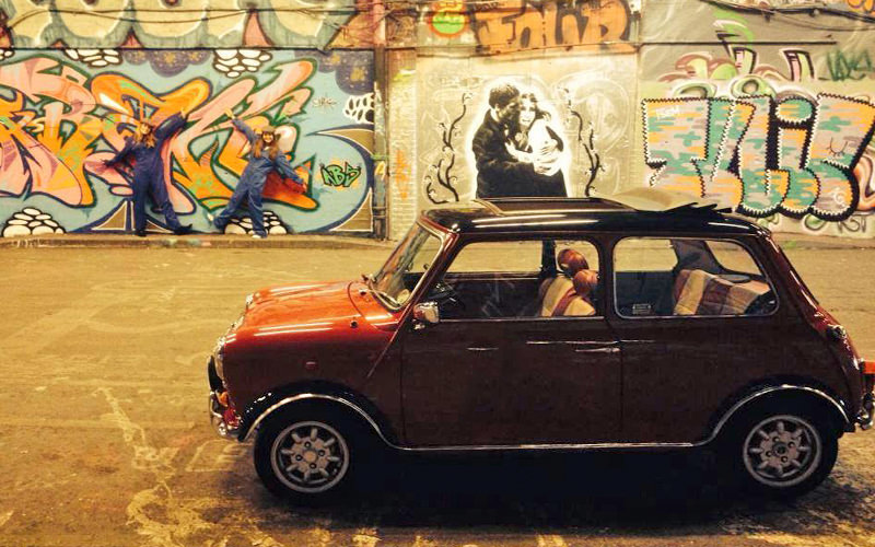An empty Mini Cooper parked in a graffitied area