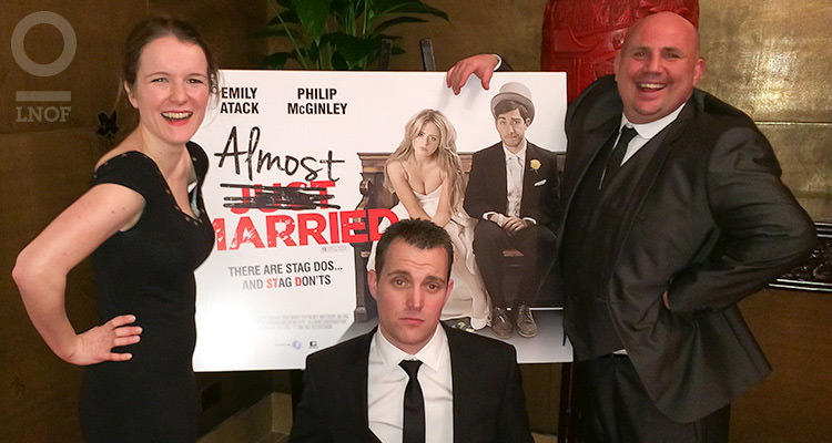 Two men and a woman posing alongside the film poster for Almost Married
