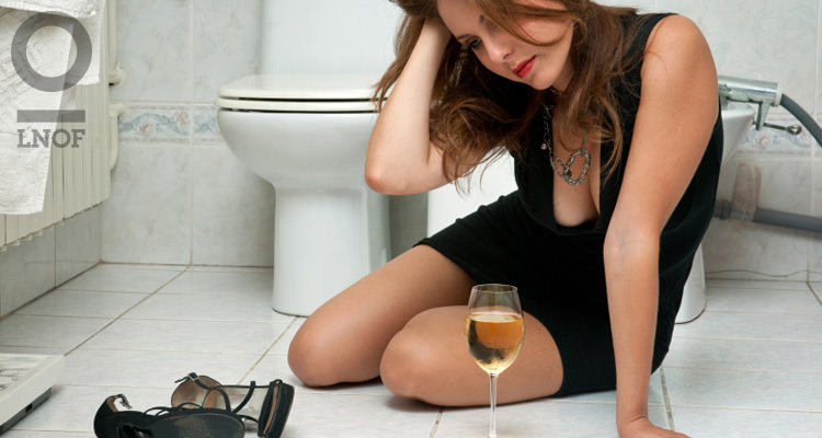 Woman sitting on toilet floor with shoes off and a glass of wine