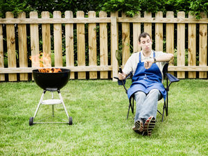 Man sitting on a chair on the lawn, looking at his watch, with a lit BBQ beside him