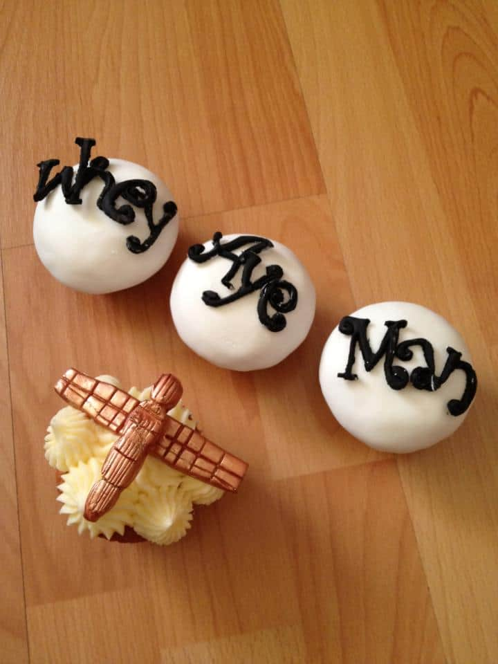 Three white cupcakes topped with Geordie writing in black, and one topped with the Angel of the North made from icing